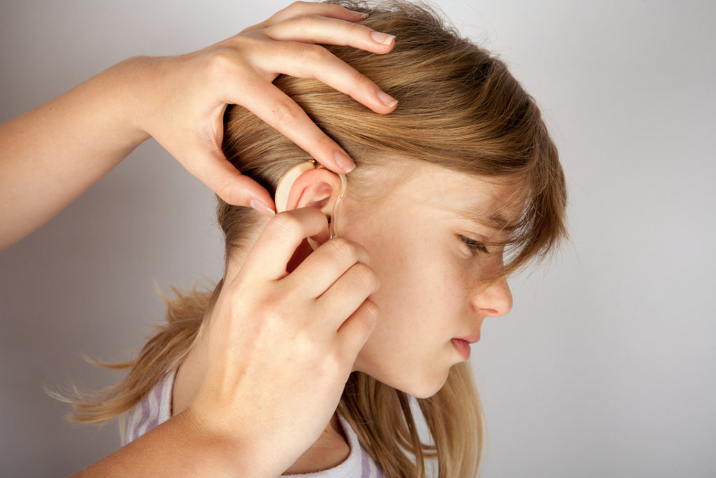 Audiologist's hands insterting a hearing aid in a young girl's ear